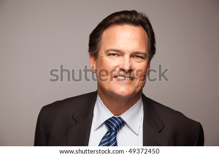 Handsome Businessman Smiling in Suit and Tie Isolated on a Grey Background.