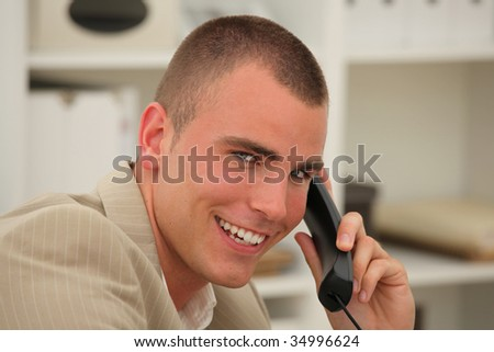Handsome businessman smiling while being on the phone in an office - stock photo