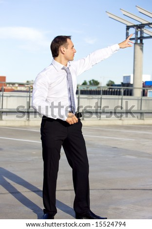 handsome businessman standing in a front of a building site
