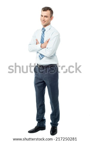 Handsome businessman standing with arms crossed - stock photo