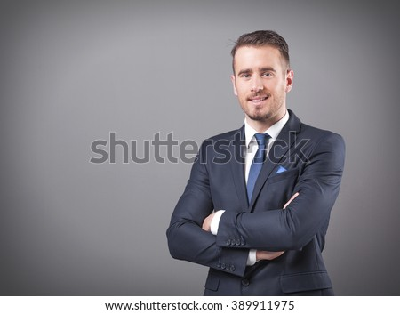 Handsome businessman standing with arms crossed on grey background - stock photo