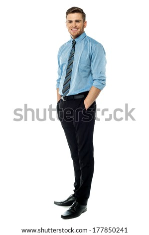 Handsome businessman standing with hands in his pocket - stock photo