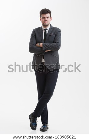 Handsome  businessman stands at full height with crossed legs .