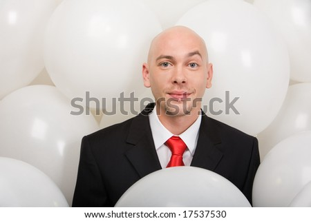Handsome businessman surrounded by many balloons looking at camera with smile - stock photo