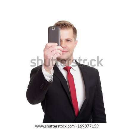Handsome businessman taking a selfie with a mobile phone - stock photo