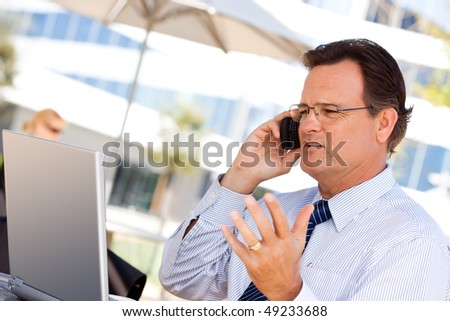 Handsome Businessman Talking on His Cell Phone and Working on the Laptop Outdoors. - stock photo
