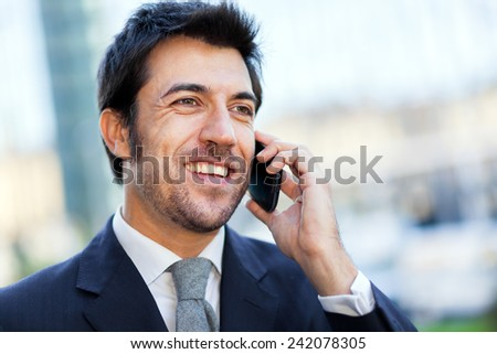 Handsome businessman talking on the mobile phone - stock photo