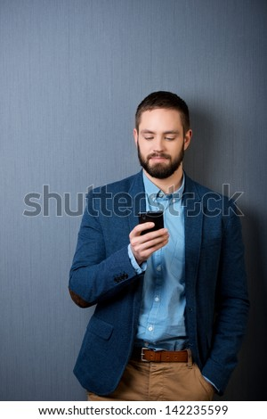 Handsome businessman text messaging on mobile phone isolated over blue background - stock photo