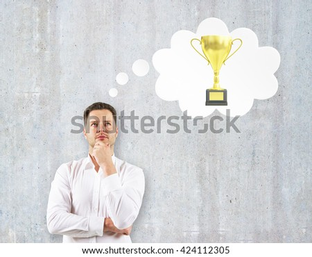 Handsome businessman thinking about golden cup trophy on concrete wall background