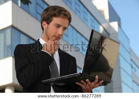 Handsome businessman using a laptop in the city - stock photo