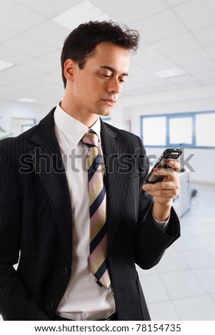 Handsome businessman using a smartphone. Isolated on white - stock photo