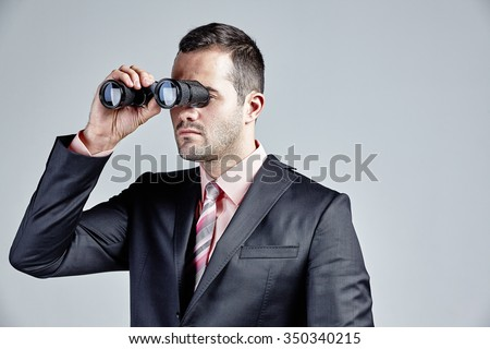 Handsome businessman using binocular isolated over grey