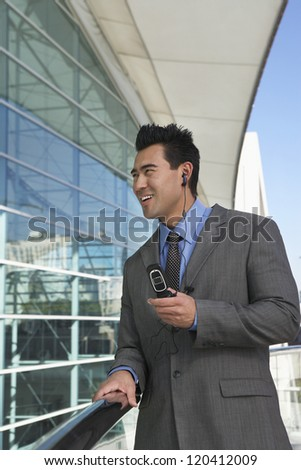 Handsome businessman using cell phone outside office