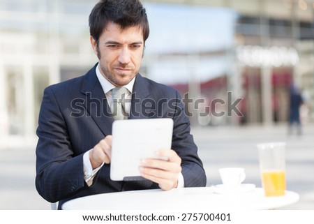 Handsome businessman using his digital tablet - stock photo
