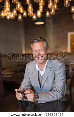 Handsome businessman using his phone at the cafe - stock photo