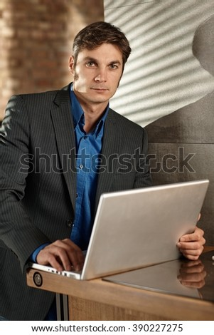Handsome businessman using laptop computer, looking at camera. - stock photo