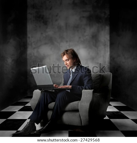 handsome businessman using laptop in a modern interior - stock photo