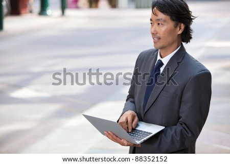Handsome businessman using laptop outdoors - stock photo