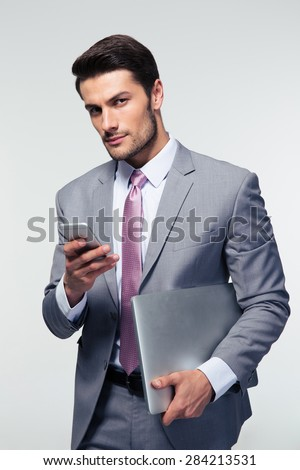 Handsome businessman using smartphone and holding laptop over gray background. Looking camera