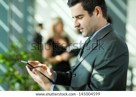 handsome businessman using tablet computer in modern office - stock photo