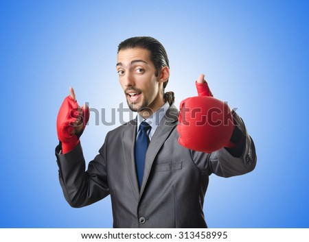 Handsome businessman with boxing gloves - stock photo