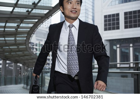 Handsome businessman with briefcase walking on footbridge - stock photo