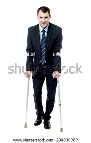 Handsome businessman with crutches trying to walk - stock photo