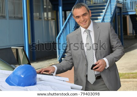 Handsome businessman with hardhat and plans - stock photo