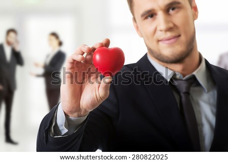 Handsome businessman with heart model.