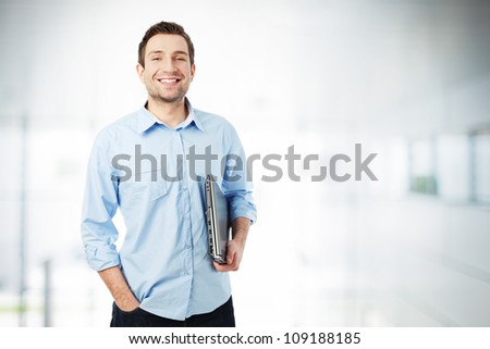Handsome businessman with laptop standing - stock photo