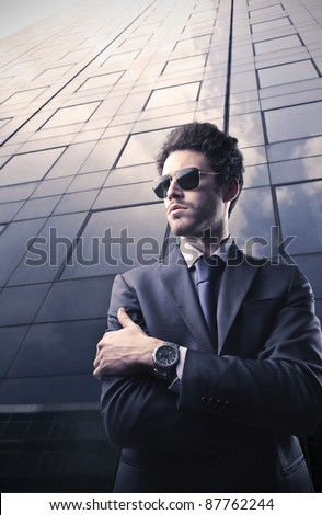 Handsome businessman with skyscraper in the background - stock photo
