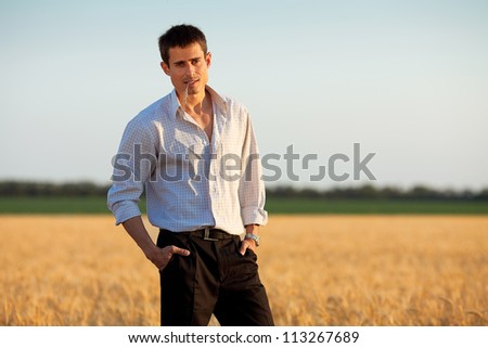 handsome businessman with spikelet in his mouth standing  in a wheat field. outdoor shot