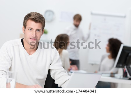 Handsome businessman working in a busy office sitting looking at the camera with a friendly smile