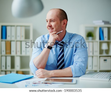 Handsome businessman working in office - stock photo
