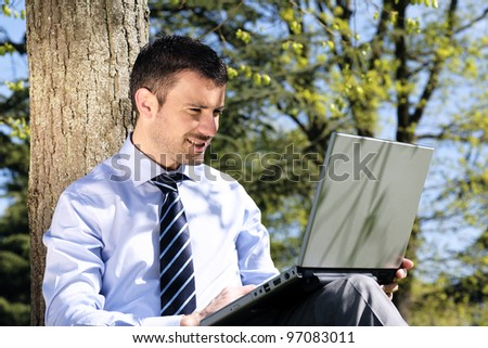 handsome businessman working on laptop in a park - stock photo