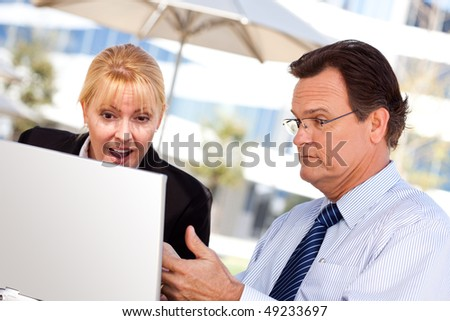 Handsome Businessman Working on the Laptop with Attractive Female Colleague Outdoors. - stock photo