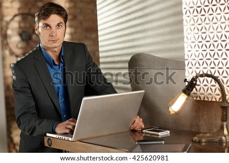 Handsome businessman working with laptop computer, looking at camera. - stock photo