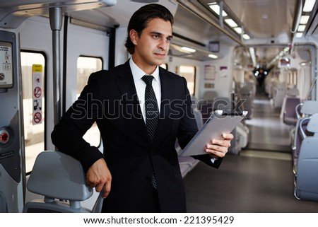 Handsome businessman working with tablet on the way to work, young executive going in train, businesspeople using technology for work, business man using the new media technologies and devices  - stock photo