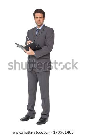 Handsome businessman writing in his diary on white background - stock photo