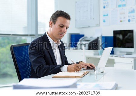 Handsome businessman writing in notepad while sitting at his table