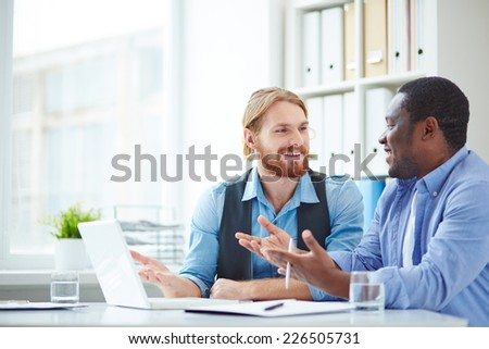 Handsome businessmen in casual sharing ideas about new points of project - stock photo