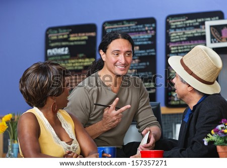 Handsome cafe owner with diverse customers taking orders - stock photo