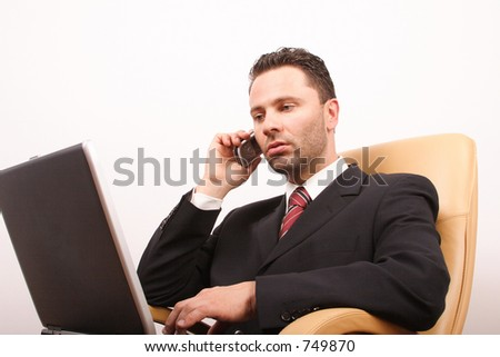 Handsome calling businessman with laptop sitting on leather armchair