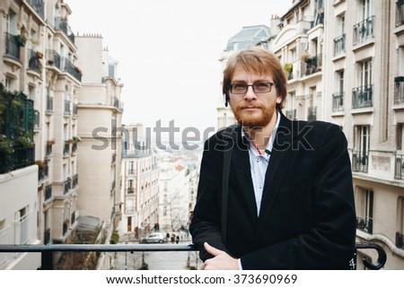 Handsome Calm Bearded Man Wearing Headset in Paris, France Looking in Camera. City Lifestyle.  - stock photo