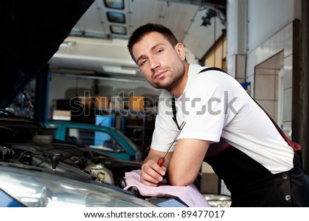 handsome car mechanic in auto repair shop
