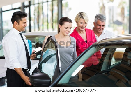 handsome car salesman showing a new car to a family - stock photo