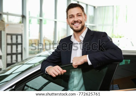 Handsome car salesman standing near automobile in dealership centre