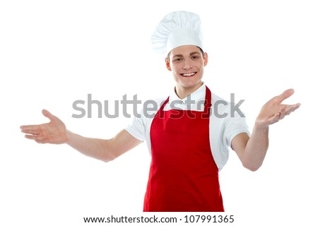 Handsome carefree male chef in a welcoming gesture isolated on white background - stock photo