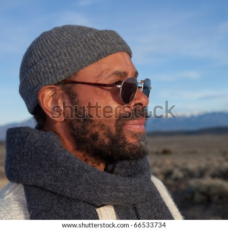 Handsome casual African American man relaxing outdoors in afternoon sun. - stock photo
