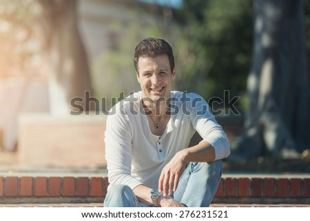 Handsome casual happy man sitting on stairs, looking away. - stock photo